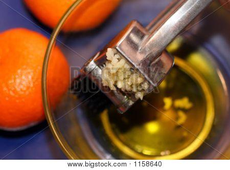 Prensa de ajo en un tazón de vidrio con naranjas en el lado