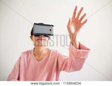 Woman looking though vr device and hand want to touch something