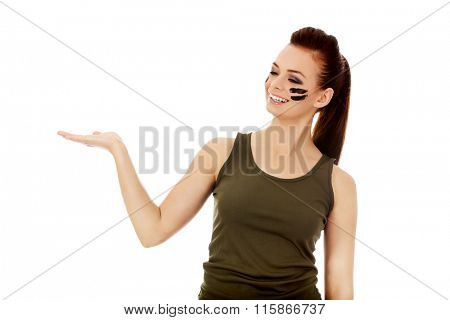 Young soldier woman presenting something on open palm