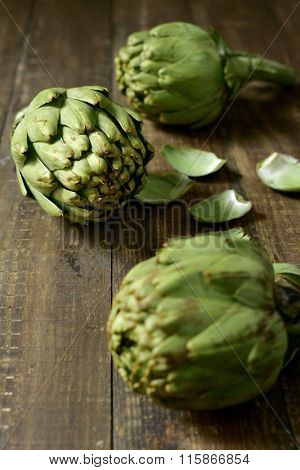 closeup of some raw artichokes on a dark wooden surface
