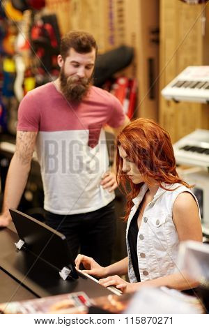 man and woman playing piano at music store