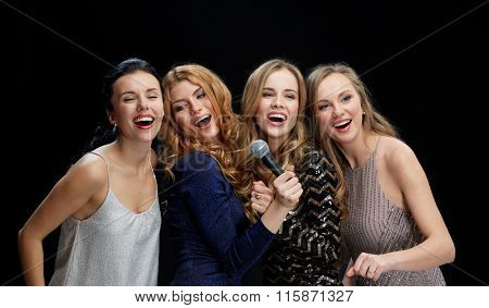 happy young women with microphone singing karaoke