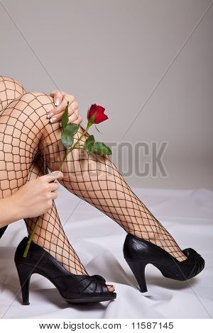 Nude caucasian woman holding red rose
