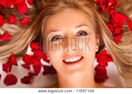 Portrait Of Caucasian Woman Laying With Rose Petals In Hair