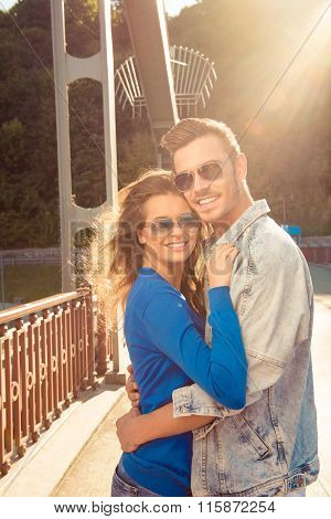Positive Funny Couple In Love On The Bridge Huging Together