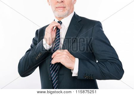 Close Up Portrait Of Old Businessman Correcting His Tie