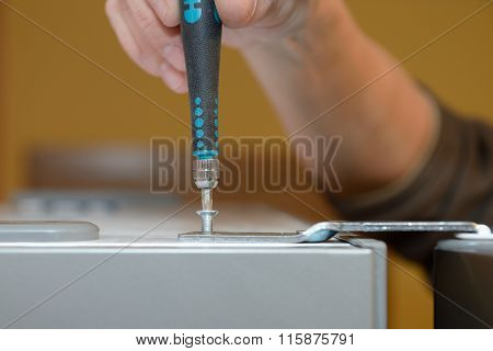 Worker twists the screw with a screwdriver