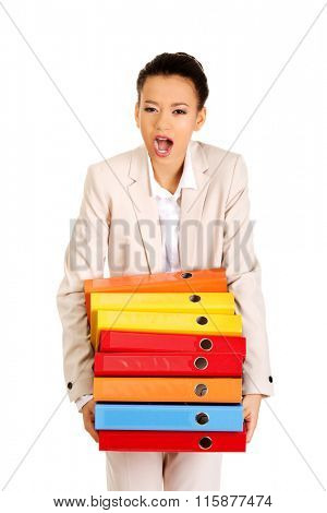 Businesswoman holding heavy bidners.