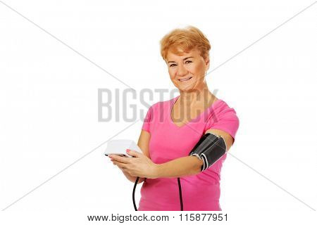 Senior woman measuring blood pressure with automatic manometer