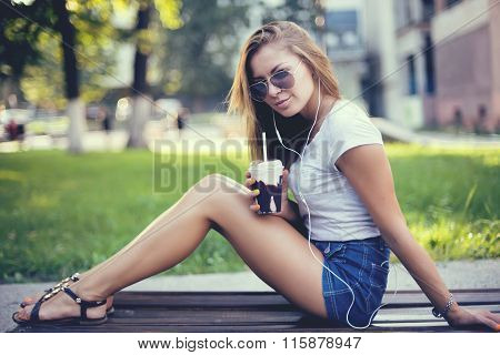 pretty smiling girl with milk shake sitting on bench at street cafe