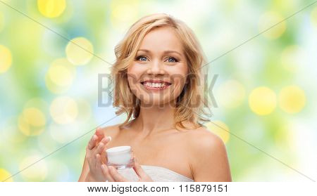 happy middle aged woman with cream jar