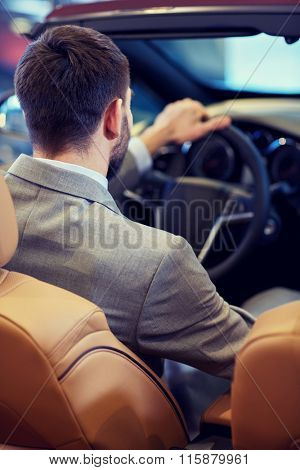 close up of man in cabriolet car at auto show