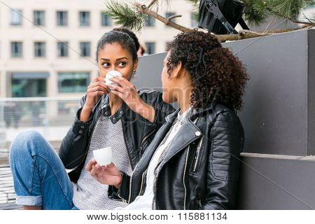 Two north African teen friends drinking together coffee outside