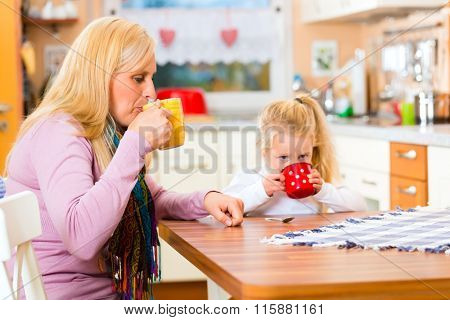 Mother and child drinking cup or mug of milk in the domestic kitchen
