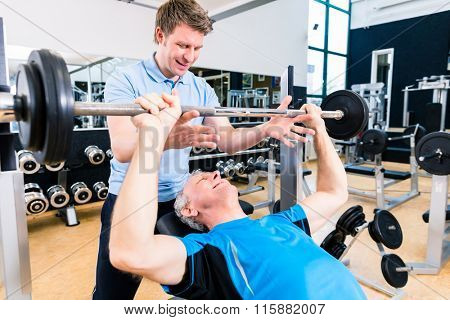 Trainer assisting senior man lifting barbell in gym to gain strength and fitness