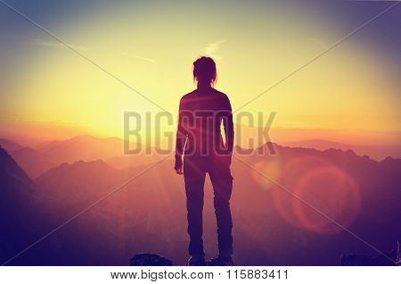 Hiker on a mountain top at sunset.
