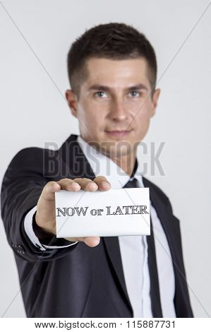 Now Or Later - Young Businessman Holding A White Card With Text