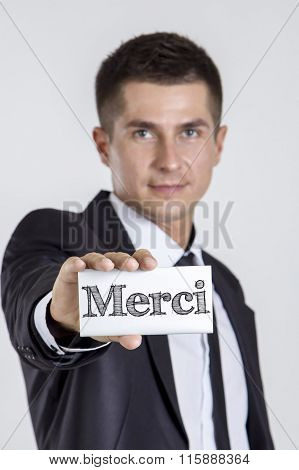 Merci - Thank you - Young Businessman Holding A White Card With Text