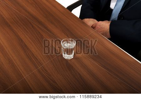 Glass of clear vodka on the desk