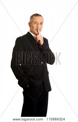 Mature businessman gesturing silent sign