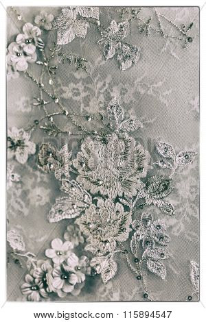 A Black And White Photo Of A Detailed White Wedding Dress With White Flowers And Fake Diamonds Knitt