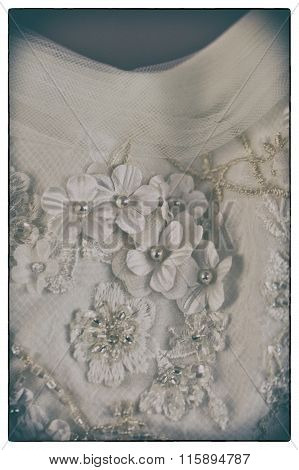 A Macro Photo Of A Detailed White Wedding Dress With White Flowers And Fake Diamonds