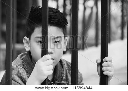 Asian Boy Behind Iron Bars