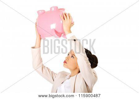 Business woman shaking piggybank.