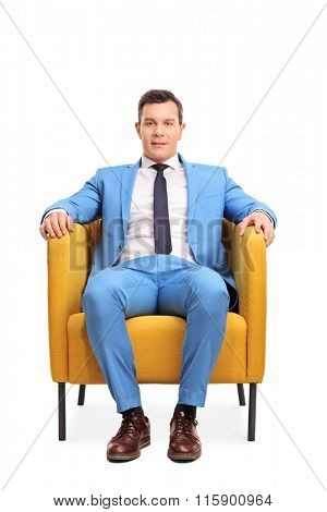 Vertical shot of a young man in an elegant blue suit sitting in an armchair isolated on white background