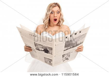 Studio shot of a surprised young bride reading a newspaper isolated on white background