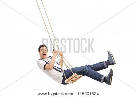 Delighted young guy swinging on a wooden swing and looking at the camera isolated on white background