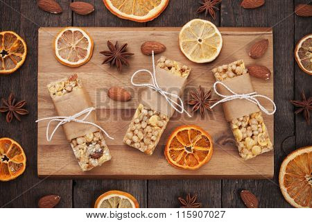 Granola bars with cereals and dried fruit on wooden board