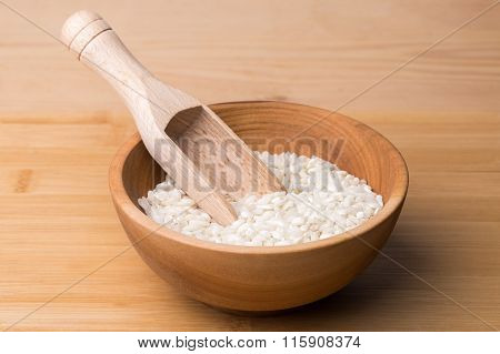 Uncooked Rice In Wooden Bowl With Spoon On A Wooden Surface