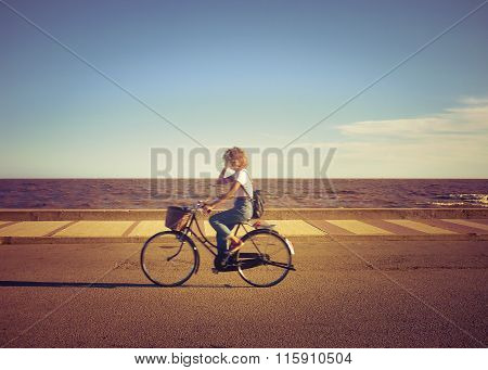 Young Woman Biking At The Boardwalk At Summer In Montevideo