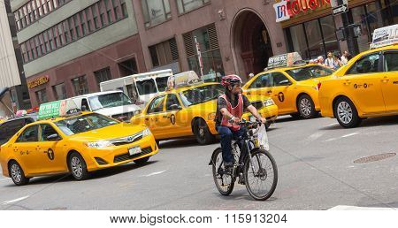 Cyclist In Traffic Between The Yellow Cabs In Manhattan, Nyc.