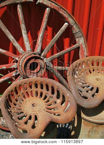 Old Wooden Wagon Wheel And Two Metal Seats