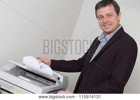 Portrait Of A Happy Business Man Using Machine