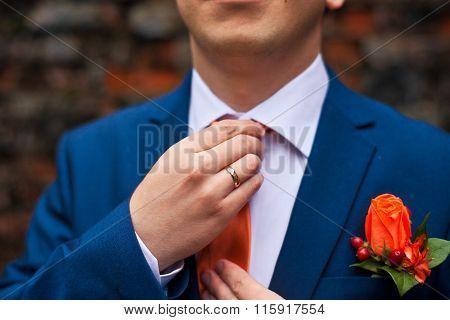 the groom in a blue suit adjusts his orange tie