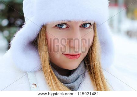 Portrait of a beautiful young woman in fur white cap on a background of a winter park