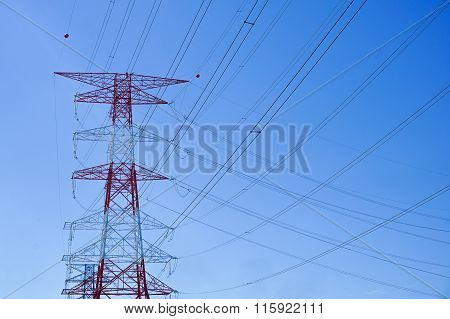 High voltage power pylons in the sky background