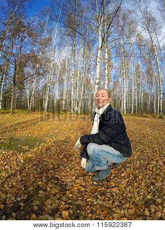 The happy woman is basked in the sun in the serene autumn day in the birch wood