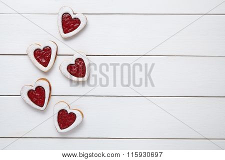 Heart shaped cookies with jam for Valentines day on white wooden background