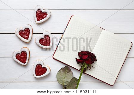 Handmade heart shaped cookies with empty notebook and rose flower on white wooden background for Val