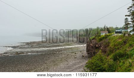 Springtime Nova Scotia coastline in June fog, people at base of cliff exploring the pebble beaches.