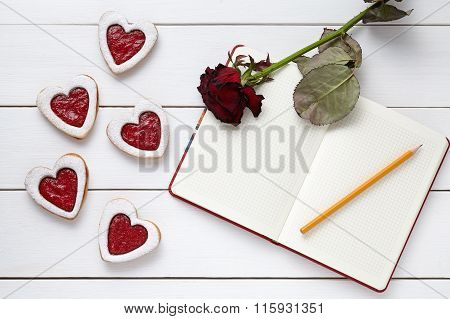 Shortbread heart shaped cookies with empty notebook, pencil and rose flower on white wooden backgrou