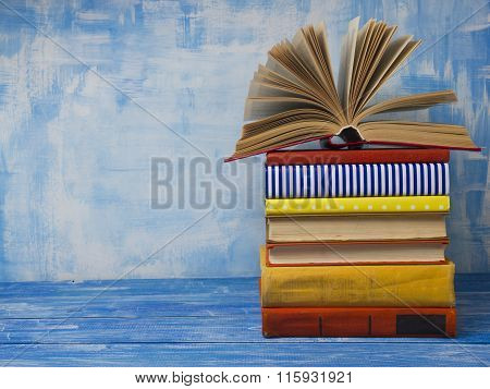 Open book, hardback books on abstract blue background at wooden table. Back to school. Copy space fo