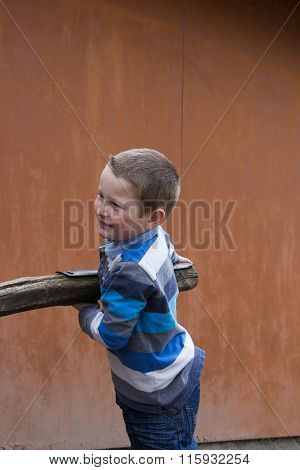 Boy Holds Wooden Beams