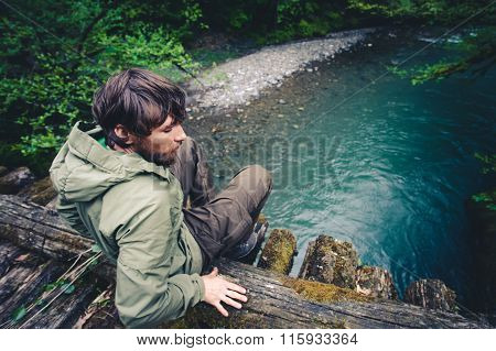 Man Traveler relaxing on wooden bridge over river Travel