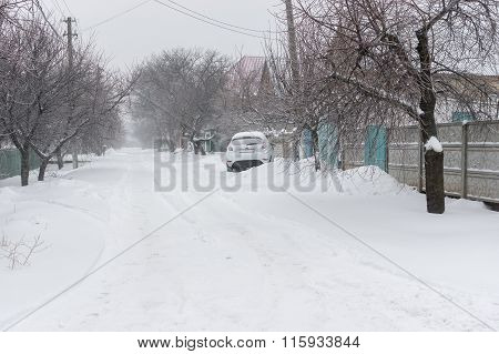 Snow-covered small street of the Dnepropetrovsk city's suburb after snowfall and icing over