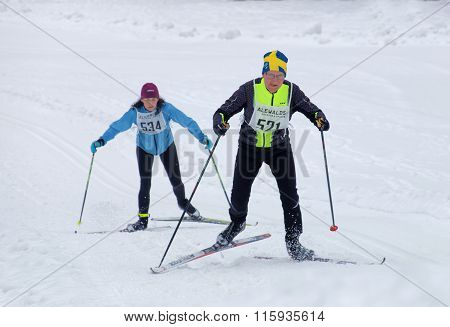 Cross Country Skiing Man Wearing Swedish Hat And Woman Skiing Uphill